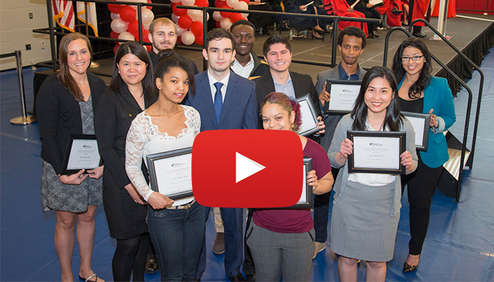 video still of students holding certificates with a play button over the image