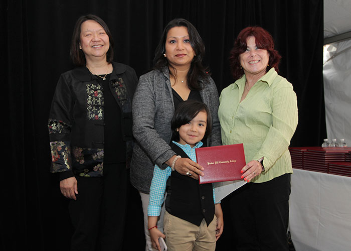 female student with her child receives diploma from Toni and president eddinger