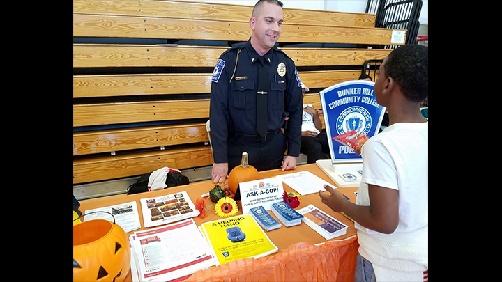 Cop on the information booth attending to a kid