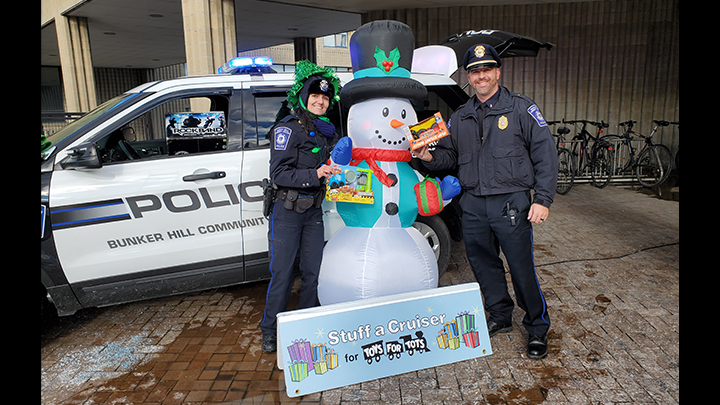 Two Cops Posing with Snowman infront of the Stuff the Toy Banner