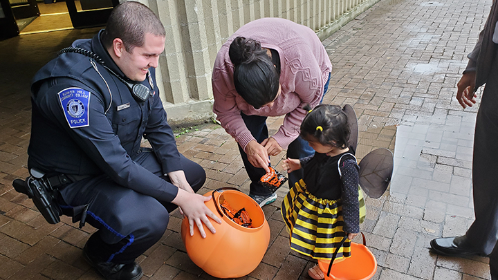 Cop participating in a trick or treats with a kid