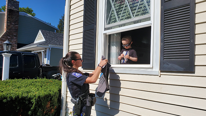 A cop giving a gift to a kid through a window.